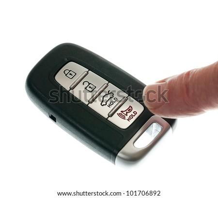 Finger pressing alarm on black modern car door opener and keyless entry device - stock photo