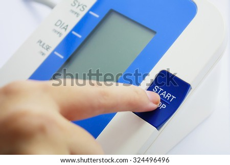 Finger pressing button of digital Blood Pressure Monitor on White background