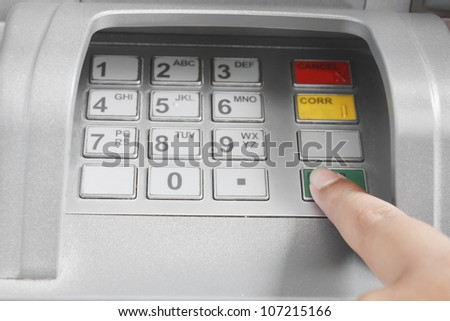 Finger pressing enter after code number insertion on ATM keyboard banking machine