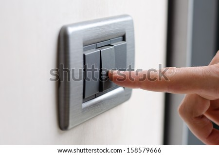 Finger pressing light switch - stock photo
