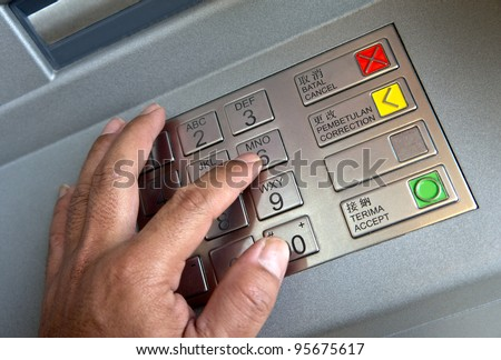 Finger pressing password number on ATM machine - stock photo