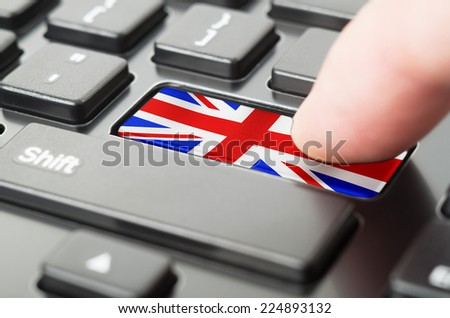Finger pressing United Kingdom key on a black keyboard - stock photo