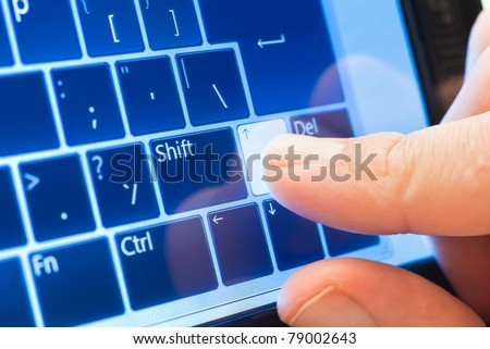 finger push arrow on touch screen virtual keyboard - stock photo