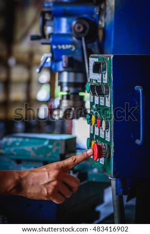 Finger push on red emergency stop switch milling machine in factory workshop.
