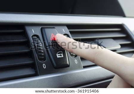 Finger pushes car emergency lights button - stock photo