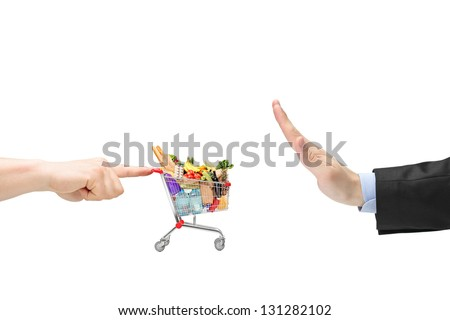 Finger pushing a shopping cart with food products and male hand gesturing stop - stock photo