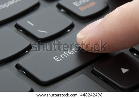 Finger pushing enter button on black computer keyboard; Macro photo - stock photo