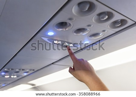 Finger show on Fasten Seat belt Sign Inside an airplane - stock photo