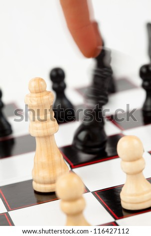 Finger taking the black king at the chessboard