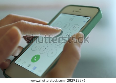 Finger touch number on smartphone to make a call, close up - stock photo