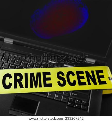 fingerprint on a laptop with crime scene tape  - stock photo