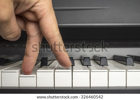 fingers click on the piano keys as if the legs are walking - stock photo