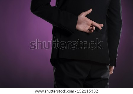 Fingers crossed. Rear view of businessman holding his fingers crossed - stock photo