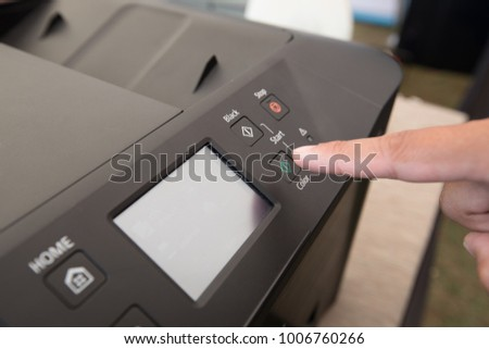 fingers hand press button on panel of copy printer