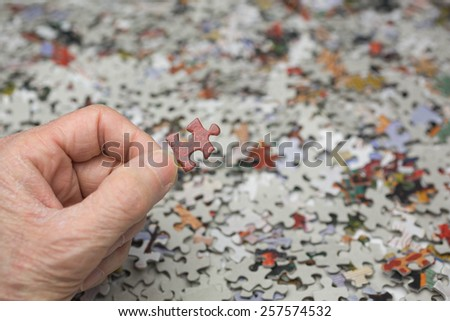 Fingers holding a single jigsaw puzzle piece against backdrop of hundreds of pieces. - stock photo