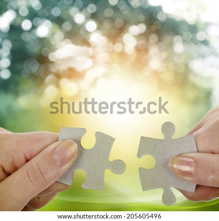 Fingers holding two puzzle pieces - stock photo