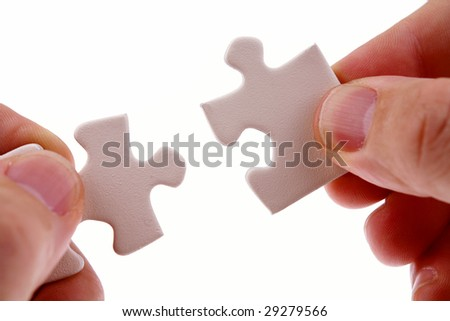 Fingers holding two puzzle pieces