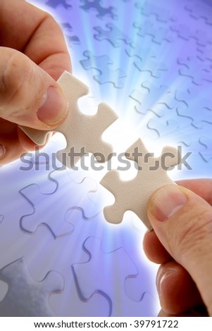 Fingers holding two puzzle pieces over bright background - stock photo