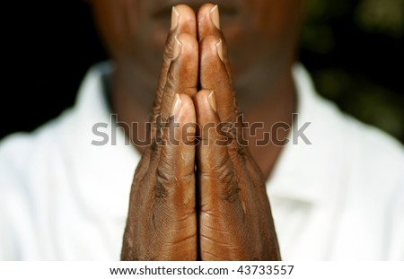 fingers of afro man in prayer - stock photo