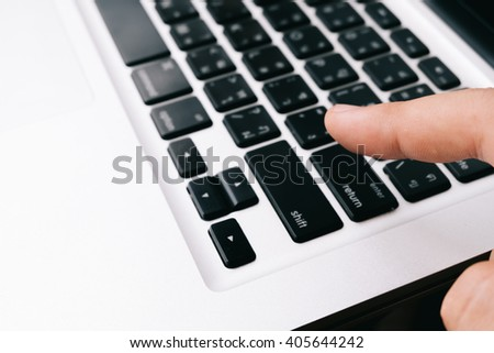 Fingers of man pressing laptop keys