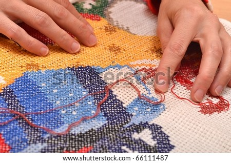 Fingers of young women, cross embroidery. - stock photo