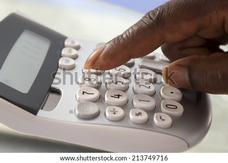 Fingers pressing on calculator keypad - stock photo