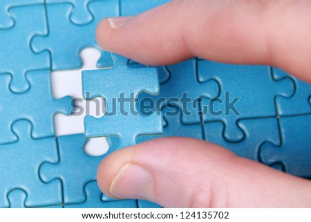 Fingers putting the last piece of puzzle in place - stock photo