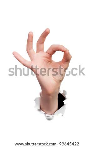 Fingers showing ok sign bursting through paper - stock photo