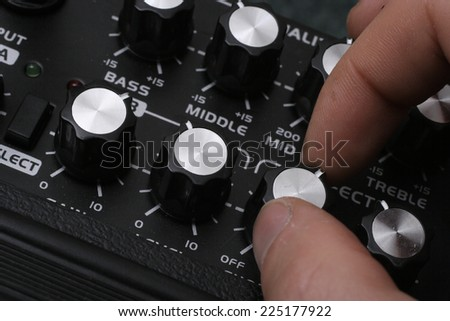 Fingers tuning a guitar amplifier.  - stock photo