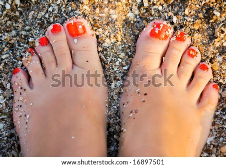 fingers wet sand at the feet of young girl