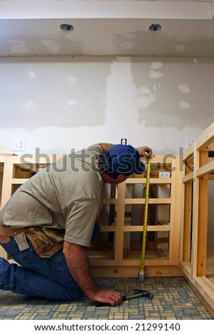 Finish carpenter working on custom home cabinets in home kitchen - stock photo