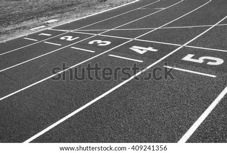 Finish line on a freshly renewed running tracks.  Image in black and white. - stock photo