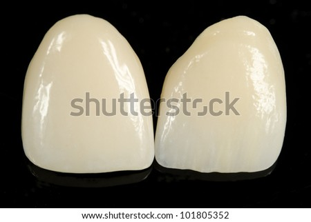 finished ceramic front crowns, black background - stock photo