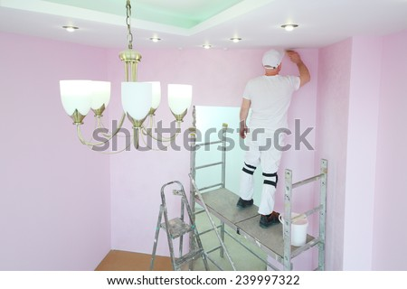 Finisher with brush in hand standing on scaffolding and painting walls in pink room - stock photo