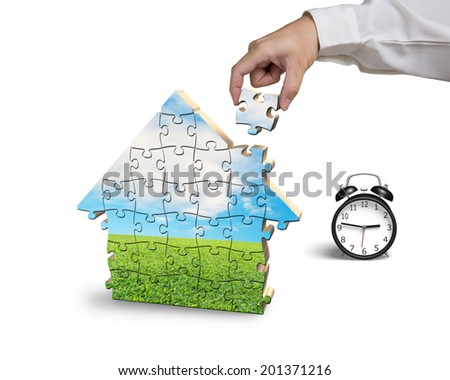 Finishing house shape puzzles assembling in white background - stock photo