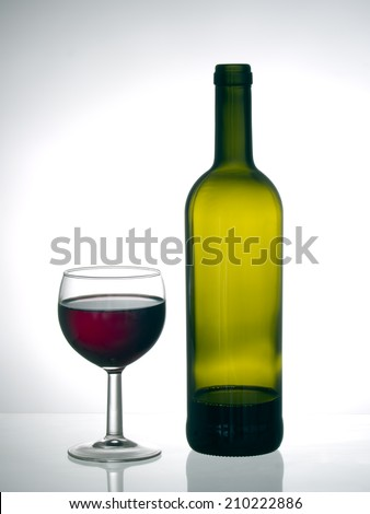 Finishing the bottle - red wine in glass with near empty bottle, backlit, grey background with copyspace. - stock photo