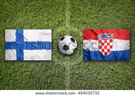 Finland and Croatia flags on a green soccer field
