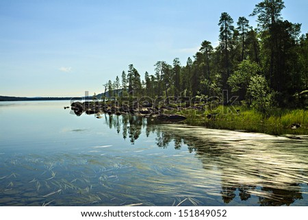 Finnish landscape with a forest lake with stones. - stock photo