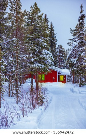 Finnish red house in snow fairy forest.