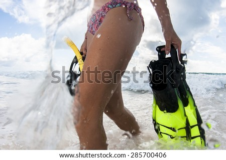 Fins, Mask and Snorkel - a girl is ready to go snorkelling off the beach. - stock photo