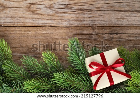 Fir branch and gift box on wooden background - stock photo