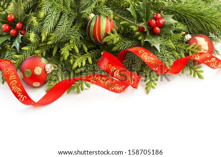 Fir tree and holly branches decoration with red ribbon for Christmas - stock photo