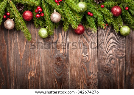 Fir tree decorated balls, cones and red berries on dark brown wooden background