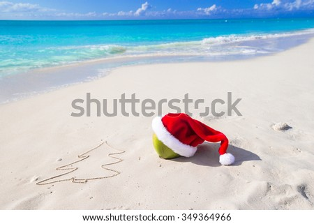 Fir-tree drawing on beach white sand with red Santa hat