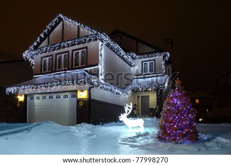 Fir-tree is decorated festoons and fairy-tale deer stand near  house - stock photo