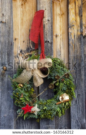 fir wreath as xmas decoration on wooden door - stock photo