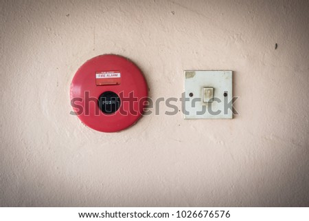 Fire alarm and switch for lights on the wall.