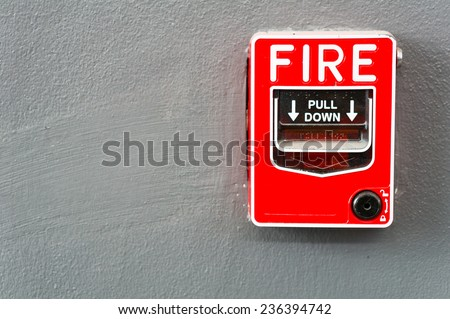 Fire alarm switch on gray wall