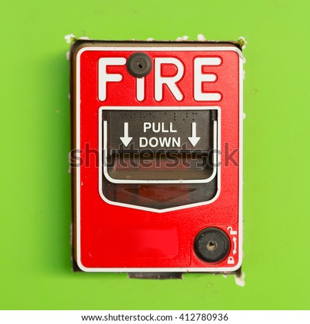 Fire alarm switch on green wall. - stock photo