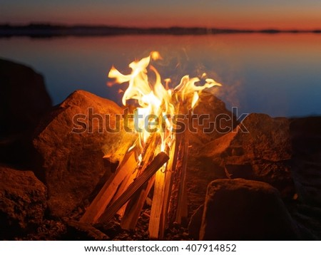 Fire and flames of atmospheric campfire on the beach at night. Still water of the lake on the background with warm colors of sunset. Very shallow dept of field.